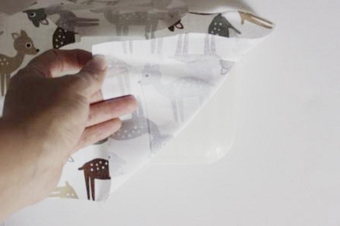 Babyspielzeug-DIY der bearbeitete Stoff wird nun so aufgeklebt, das die ausgeschnittene Stoffklappe über der Öffnung des Deckels ist, überstehender Stoff wird abgeschnitten