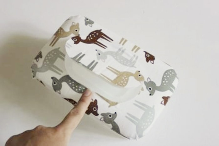 Babyspielzeug-DIY der Stoff wird auf den kleinen Deckel geklebt