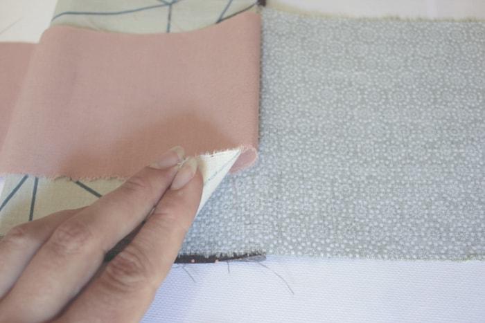 Babyspielzeug-DIY wenn ein neuer Stoffrest auf die zusammengeklappten Hälften aufgelegt wird, kann man zusätzlich einen bis zwei Zentimeter davon unter den Rand des darunter liegenden Stoffes schieben, damit beim Herausziehen der Stoffe auch der folgende sicher mit herausgezogen wird