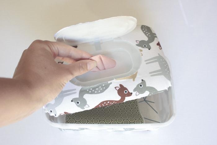 Babyspielzeug-DIY die ineinander geklappten Stoffe werden in die Box gelegt und der oberste Stoffrest von unten durch die Öffnung gefädelt